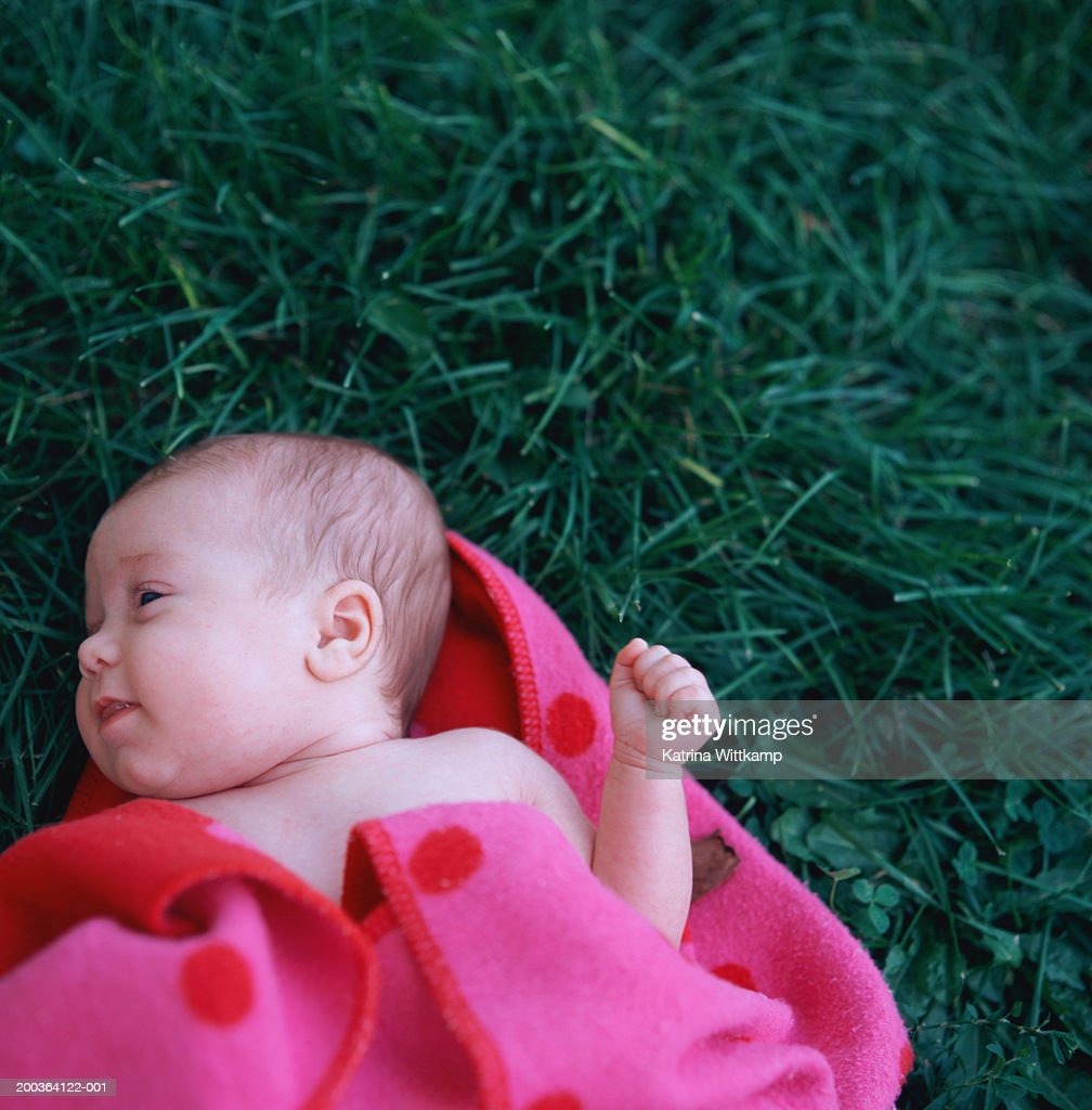 Baby girl (2-5 months) lying in blanket on grass : Stock Photo