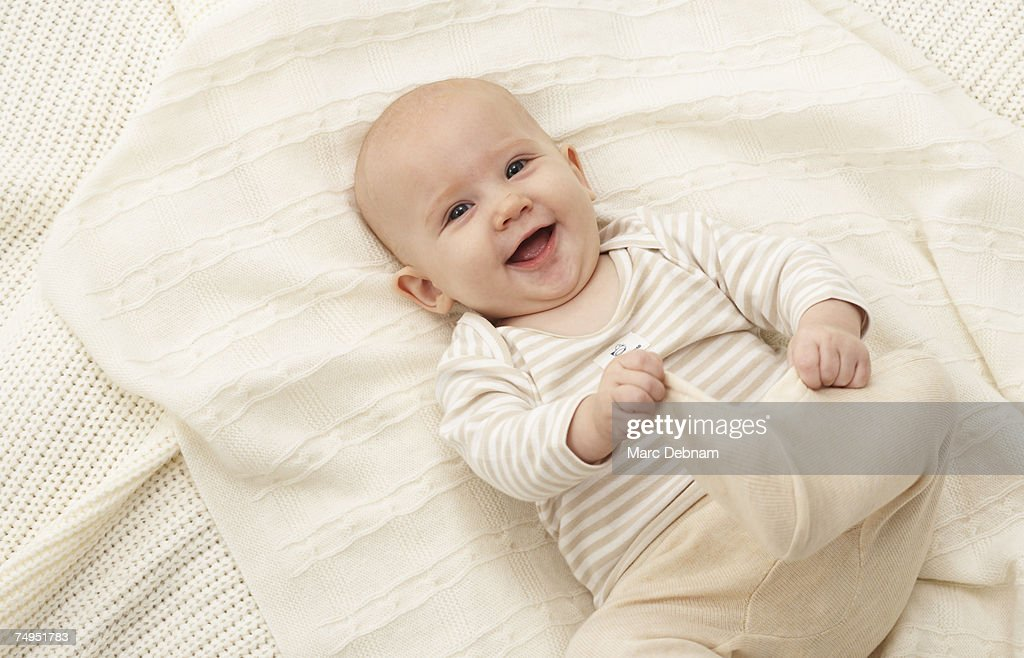 Baby girl (3-6 months) lying on blanket, smiling : Stock Photo