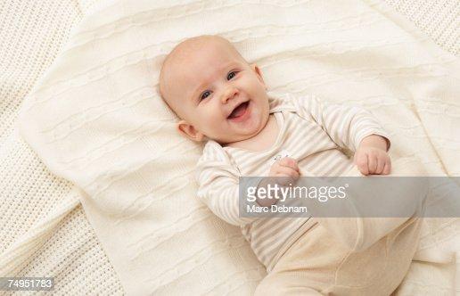 Baby girl (3-6 months) lying on blanket, smiling : ストックフォト