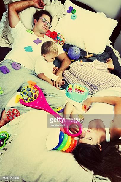 Disordinato bambino Ragazza su un letto con i genitori