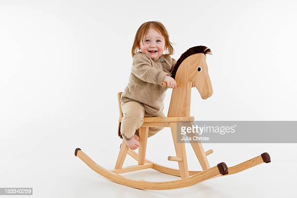 A baby girl on a rocking horse