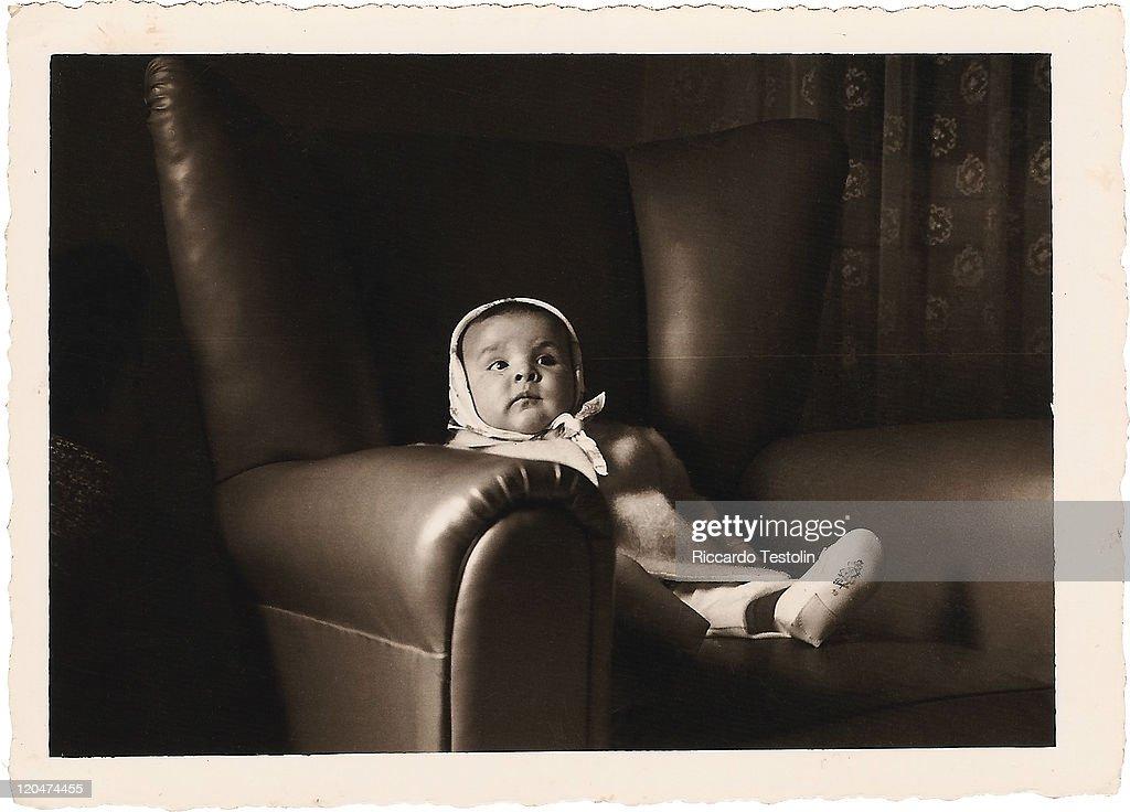 Baby girl on an armchair : Stock Photo