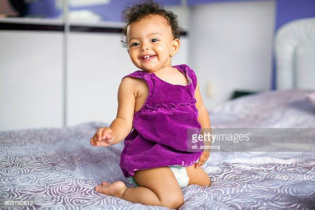 Baby girl on the bed in bedroom