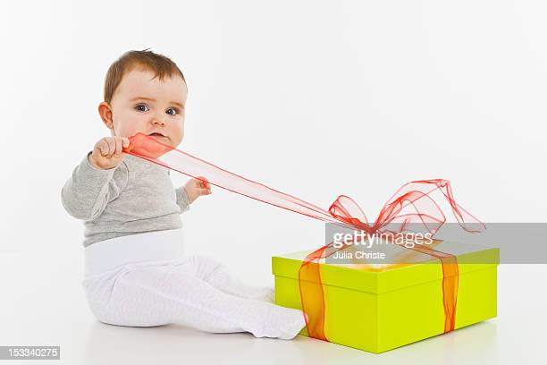 A baby girl opening a present