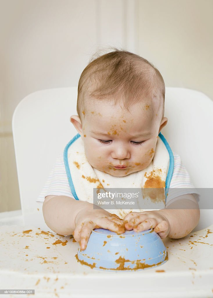 Baby girl (6-7 months) playing with bowl with food in high chair