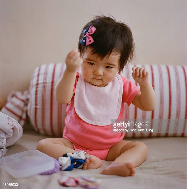 Baby girl playing with hair bows on bed.