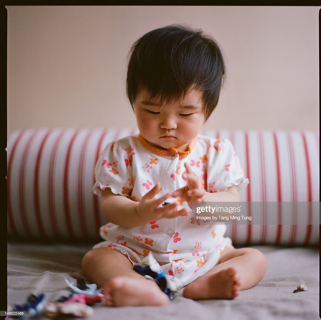 Baby girl playing with hair bows : Stock Photo