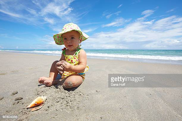 baby girl plays in sand on Florida beach