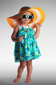 Studio portrait of cute baby girl with hat and sunglasses, summer concept