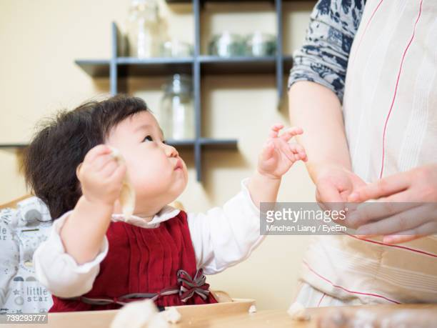 Baby Girl Preparing Jiaozi With Mother At Home