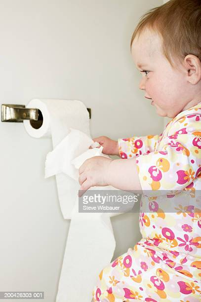 Baby girl (12-15 months) pulling toilet paper from dispenser