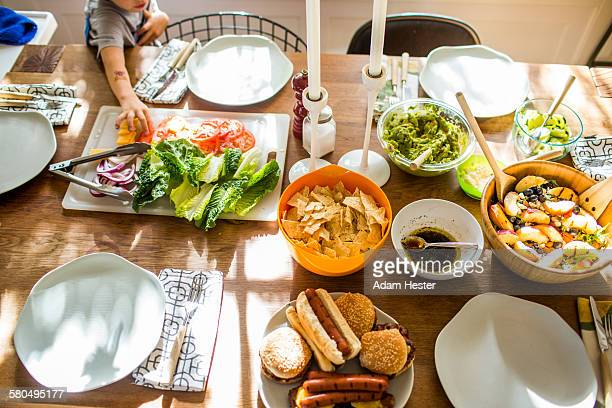 Baby girl reaching for vegetables at buffet table