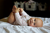 A cute 6 month old baby girl is laying on a blanket and holding her toes in her nursery.