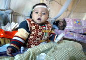 A baby girl shares a room with her mother at a maternity ward in Fumian Hospital in Yulin 09 December 2004 in southern China's Guangxi province In a...