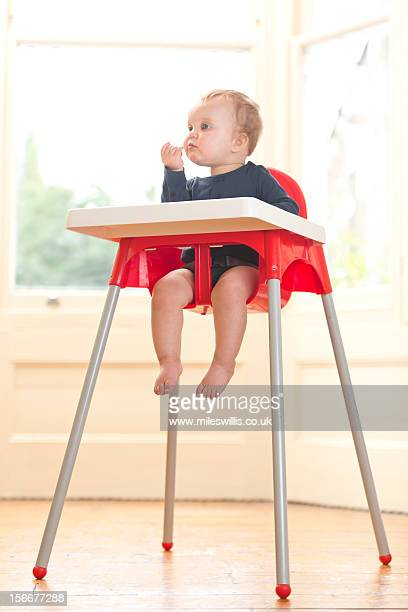 baby girl sits in high chair