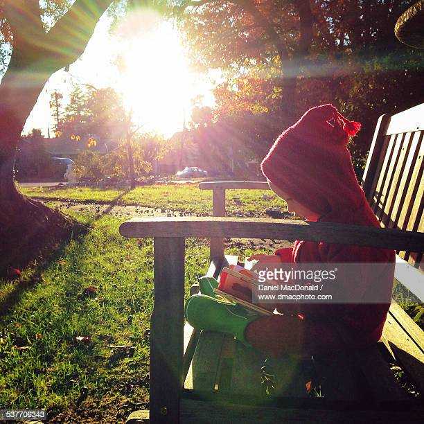 Baby girl sits on sunny bench reading a book