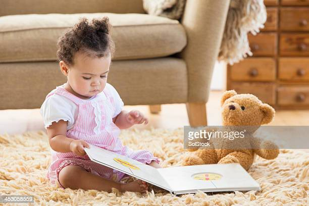 Baby Girl Sits With A Book