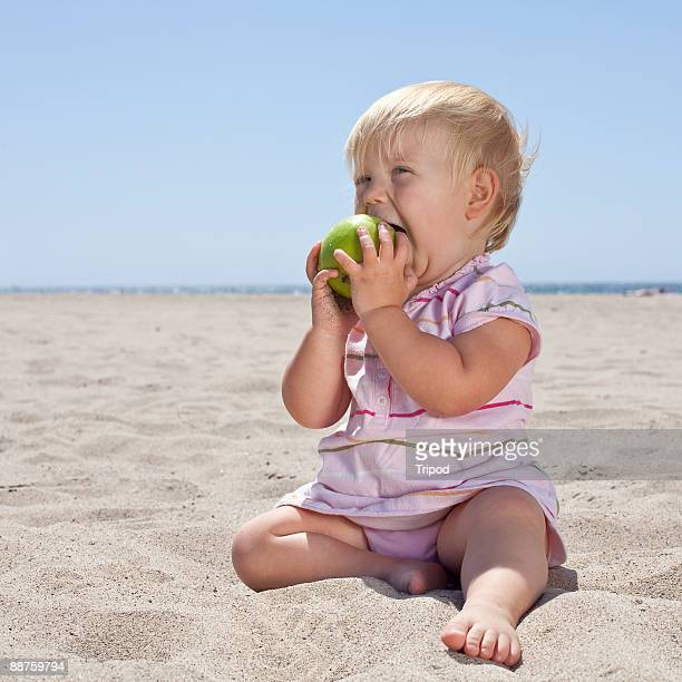 Baby girl (1-3) sitting eating apple at beach
