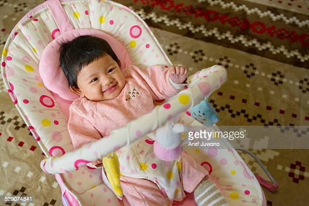 Baby girl sitting in baby bouncer