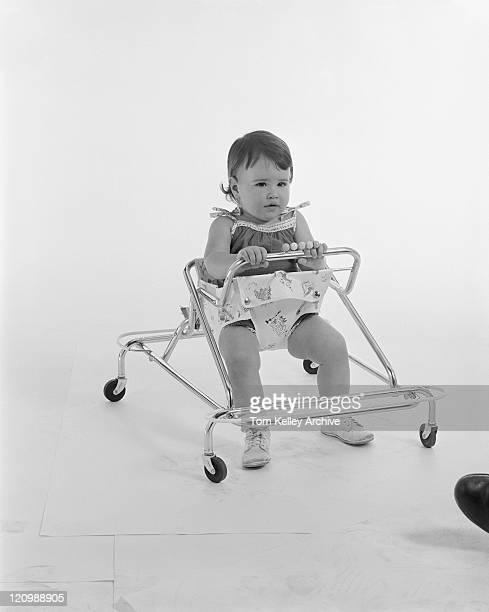 Baby girl sitting in baby walker