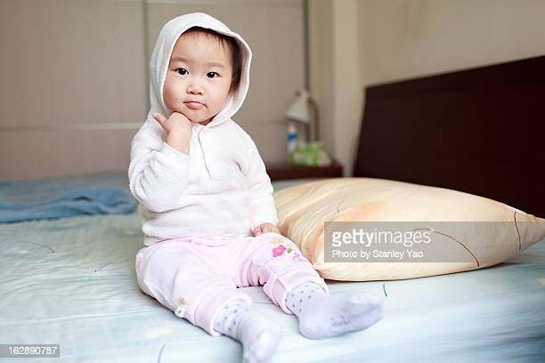 Baby girl sitting in bed