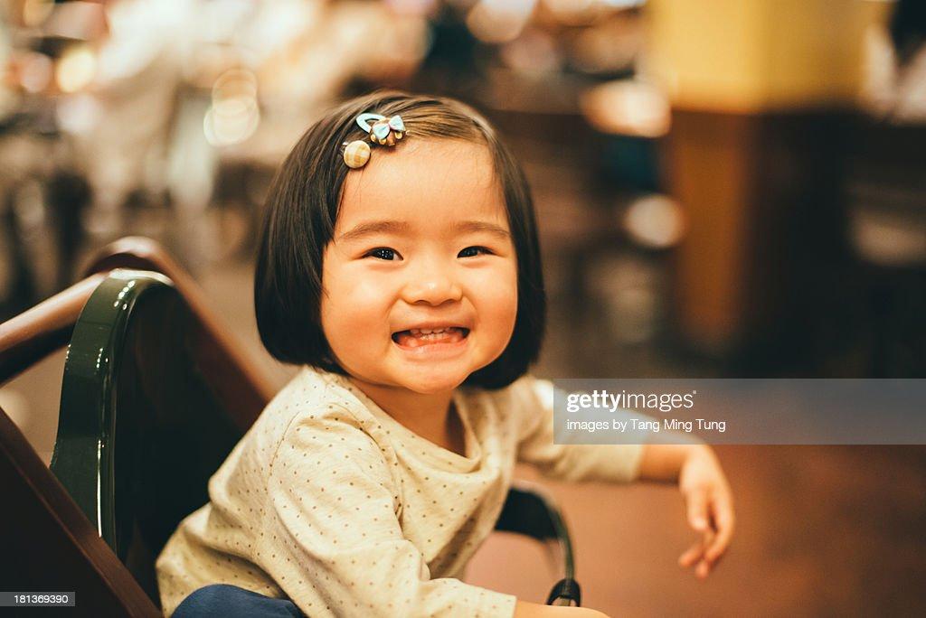 Baby girl sitting in high chair smiling joyfully : Stock Photo
