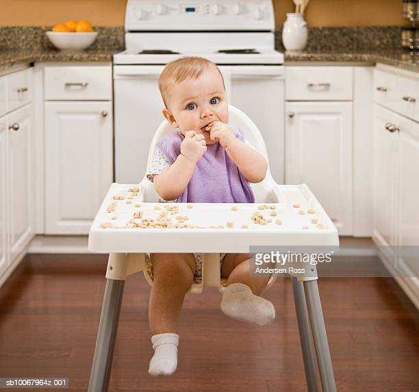 Baby girl (8 months) sitting in highchair, eating cereal, portrait