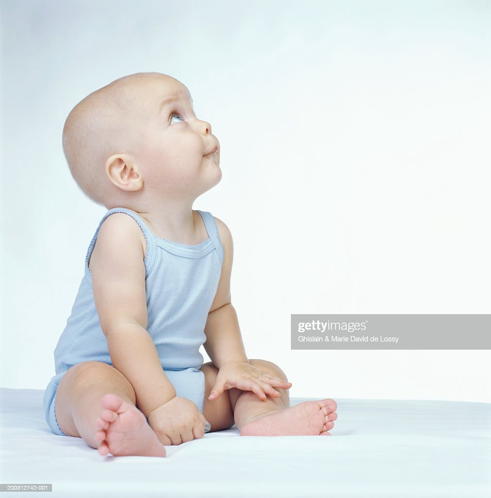Baby girl (6-9 months) sitting, looking up