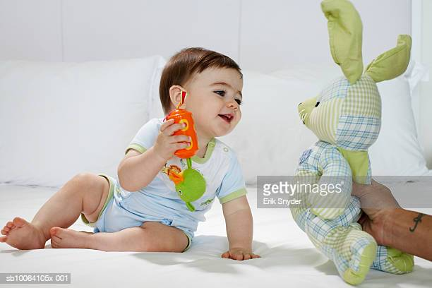 Baby girl (15-18 months) sitting on bed, man's hand holding toy rabbit