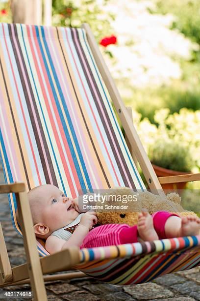 Baby girl sitting on deck chair with teddy bear