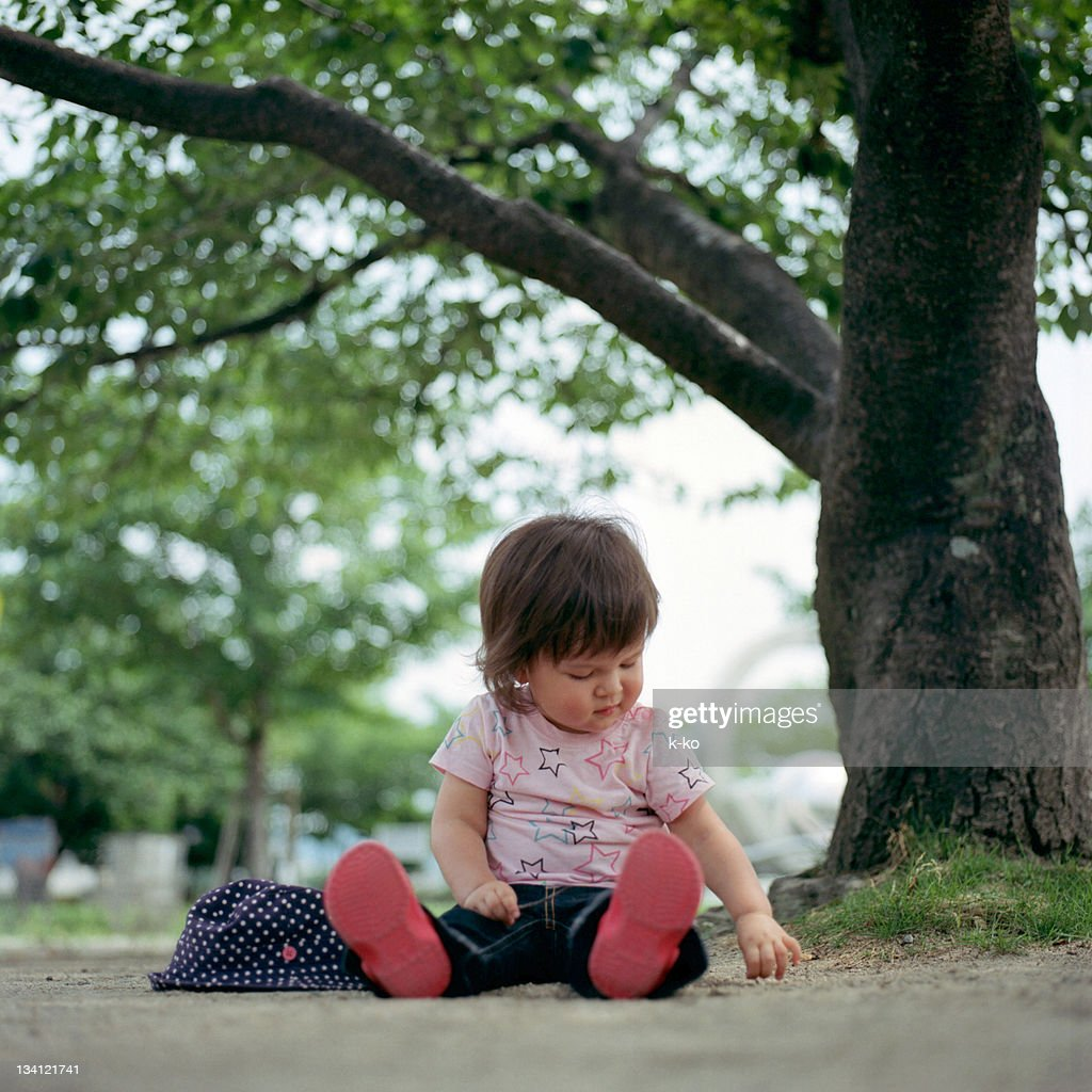 Baby girl sitting on ground : Stock Photo