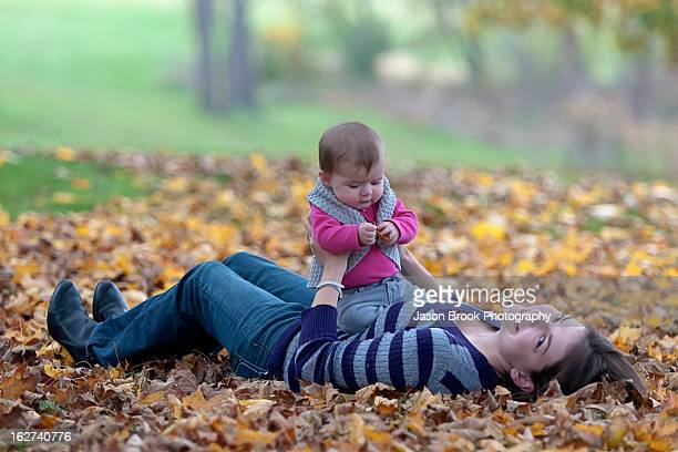 Baby girl sitting on mother in leaves