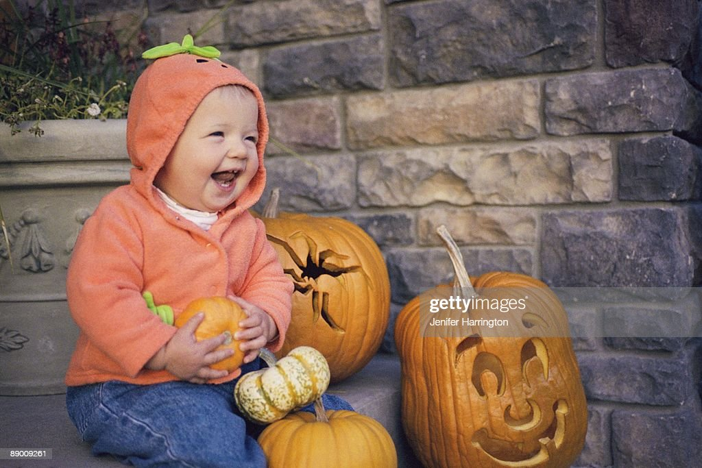 Baby girl sitting on steps by carved pumpkins : Stock Photo