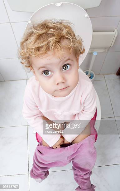 Baby girl sitting on the toilet
