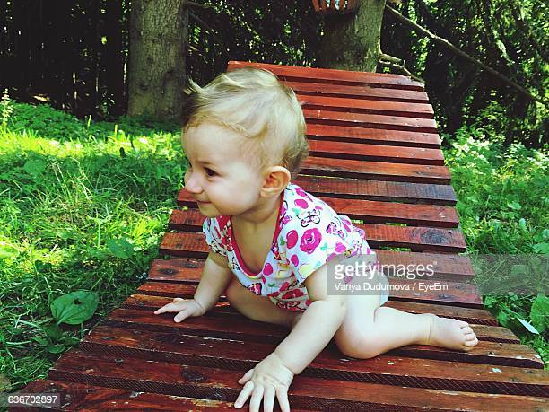 Baby Girl Sitting On Wooden Deck Chair At Field