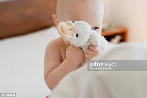 Baby girl sitting up in bed hiding behind soft toy