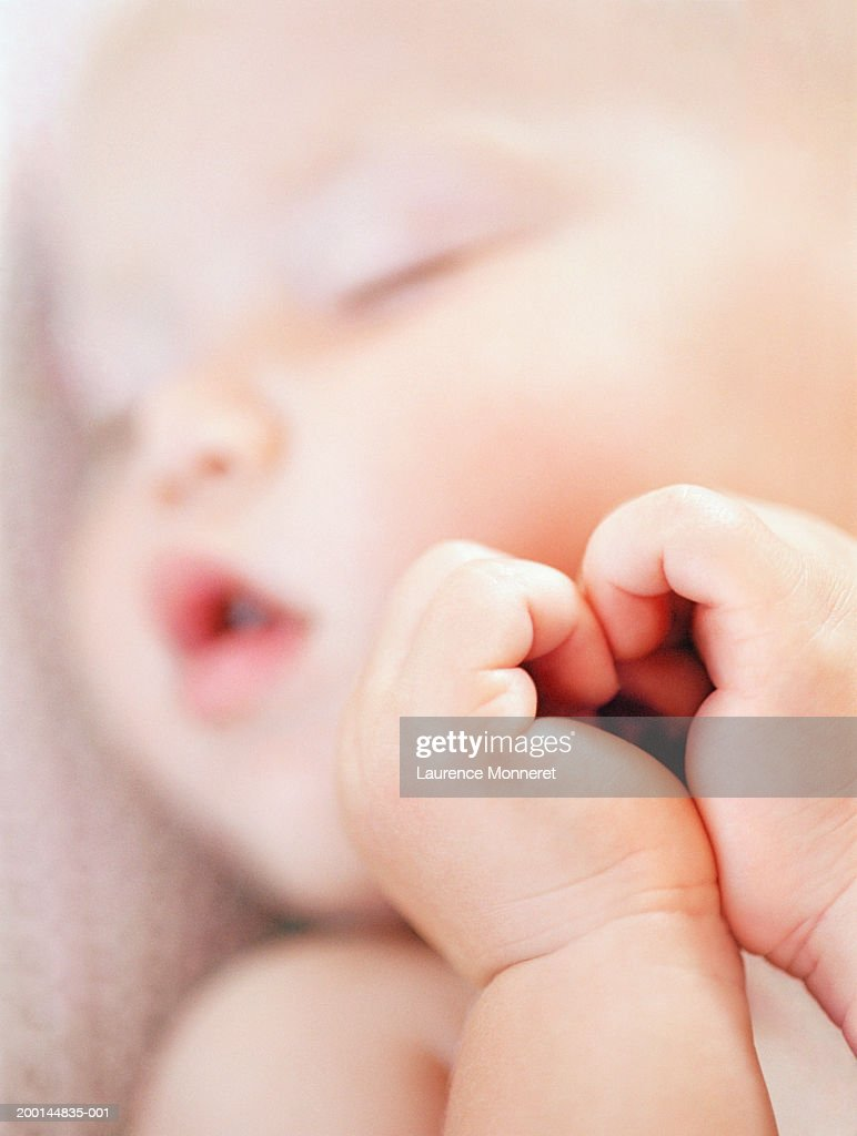 Baby girl (9-12 months) sleeping, close-up (focus on hands) : Stock Photo