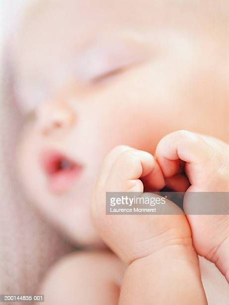 Baby girl (9-12 months) sleeping, close-up (focus on hands)