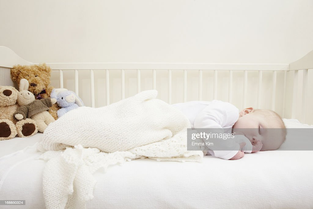 Baby girl sleeping in crib : Stock Photo
