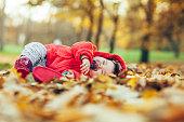Baby girl sleeping in fallen leaves