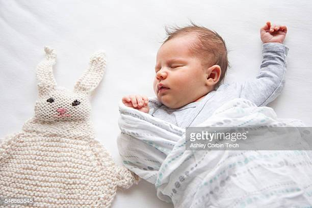 Baby girl sleeping next to knitted rabbit