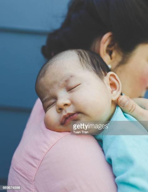 Baby girl sleeping on mothers shoulder