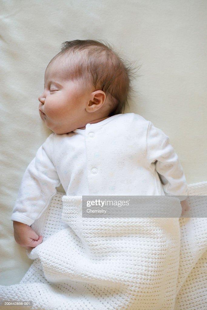 Baby girl (0-3 months) sleeping, overhead view : Stock Photo