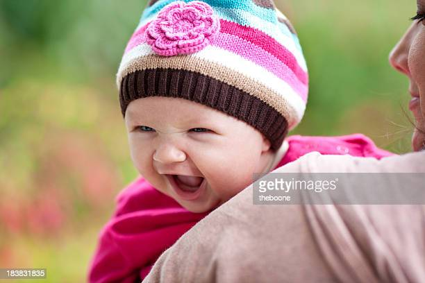 baby girl smiling in her mother's arms