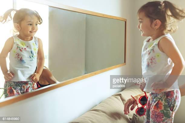 Baby girl sofa jumping at mirror