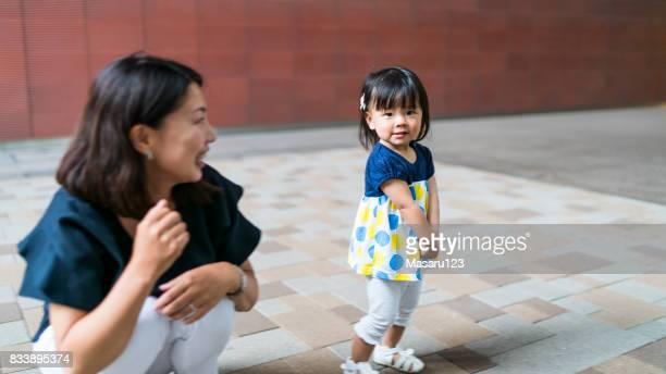 Babymädchen stehen und beobachtete sie in der Nähe von Mutter