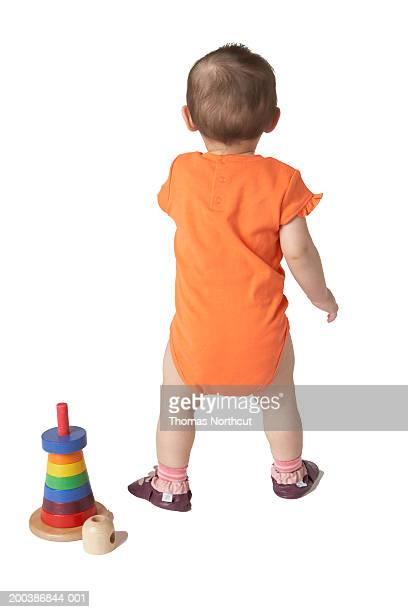 Baby girl (12-15 months) standing beside wooden toy, rear view