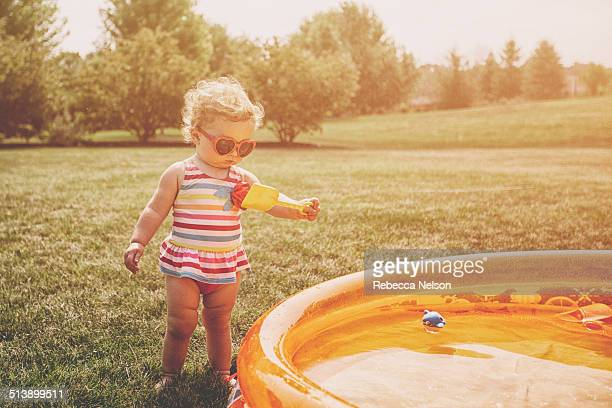 Baby girl standing next to wading pool