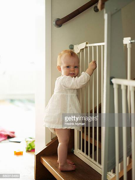 Baby girl standing on steps