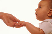 Baby girl (9-12 months)touching mother's hand, profile